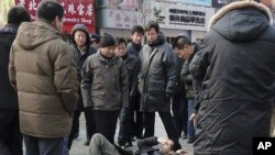 "Unidentified men surround a foreign journalist after they pushed him to the ground in the shopping street of Wangfujing, after calls for a ""Jasmine Revolution"" protest, organized through the internet, in Beijing, February 27, 2011"