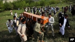 FILE - In this April 30, 2018 file photo, relatives, colleagues and friends of AFP chief photographer, Shah Marai, who was killed that day in a second suicide attack, carry his coffin in his village, Guldara, a district of Kabul province, Afghanistan. (AP