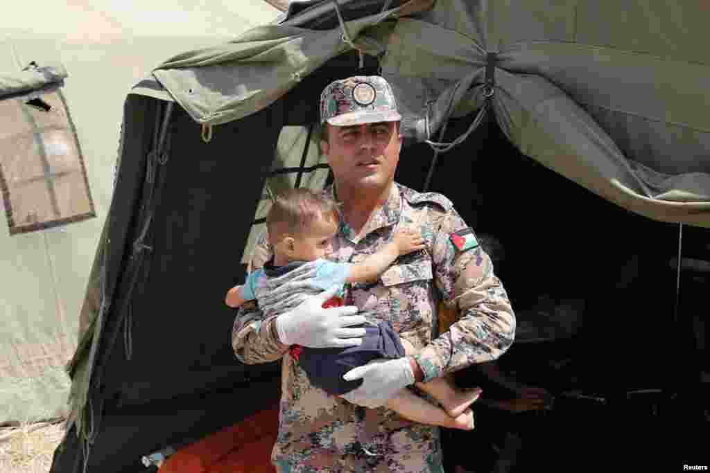یک سرباز اردنی در نزدیکی مرز سوریه کودک آواره سوری را که برای درمان و انجام معاینات پزشکی در بیمارستان صحرایی حضور یافته، حمل می کند.