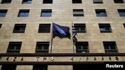 A European Union flag (L) flutters next to a Greek flag on the facade of the Bank of Greece headquarters in Athens, April 14, 2015.