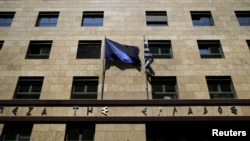 FILE - A European Union flag (L) flutters next to a Greek flag on the facade of the Bank of Greece headquarters in Athens, April 14, 2015.