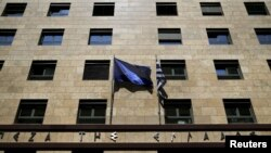 FILE - A European Union flag (L) flutters next to a Greek flag on the facade of the Bank of Greece headquarters in Athens.