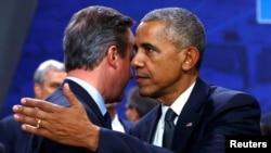 U.S. President Barack Obama embraces British Prime Minister David Cameron during a NATO Summit in Warsaw, Poland, July 8, 2016.