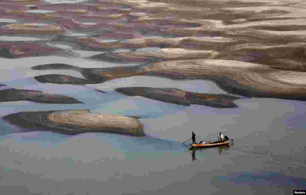 Two men row a boat past a partially dried-up riverbed on a section of the Yangtze River in Jiujiang, Jiangxi province, China.