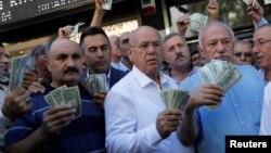 Para pengusaha Turki membawa uang dolar AS untuk mendukung seruan Erdogan agar menjual dolar mereka dalam aksi di Ankara, Turki.