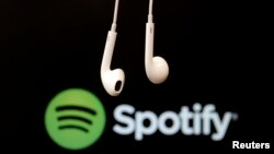 FILE - Headphones are seen in front of a logo of online music streaming service Spotify.