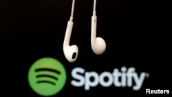 Earphone menggantung di depan logo layanan aliran musik Internet, Spotify.