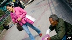 在广州,妇女行人走过一名乞丐。尽管中国经济大发展,但穷人依旧很多