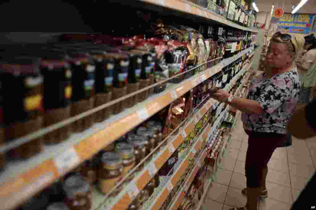 A woman shops for sweets from an assortment of imported food stuffs at a supermarket in downtown Moscow, Aug. 7, 2014.