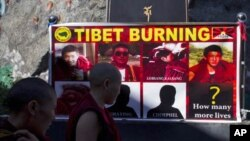 Tibetan Buddhist nuns look at a poster showing pictures of those who self-immolated since March in Tibet after a prayer session led by the Dalai Lama in Dharmsala, India, Wednesday, Oct. 19, 2011. The prayer session was to remember Tibetans who immolated