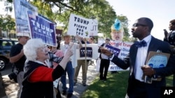 Minister Martez Thompson, right, faces backers of GOP presidential nominee Donald Trump demonstrating during Democratic rival Hillary Clinton's campaign stop at Wayne State University in Detroit, Mich., Oct. 10, 2016.