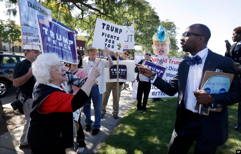 """在底特律,一位支持克林顿的黑人牧师同川普支持者争论。有标语说""""川普为你而战"""""""