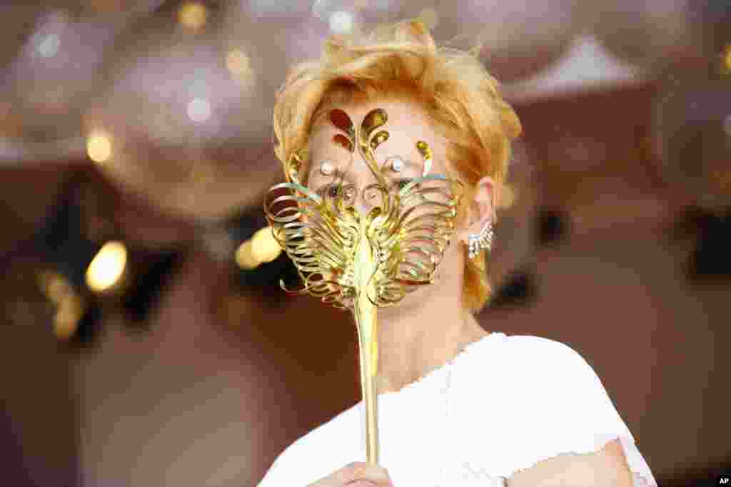 Actress Tilda Swinton holds a carnival mask as she stands for photographers while arriving at the opening ceremony of the 77th edition of the Venice Film Festival in Venice, Italy.