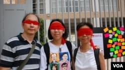 香港市民丁先生(左)與女兒(中)及太太以紅色紗布蒙眼遊行,要求當局撤回洗腦國民教育 (美國之音湯惠芸)