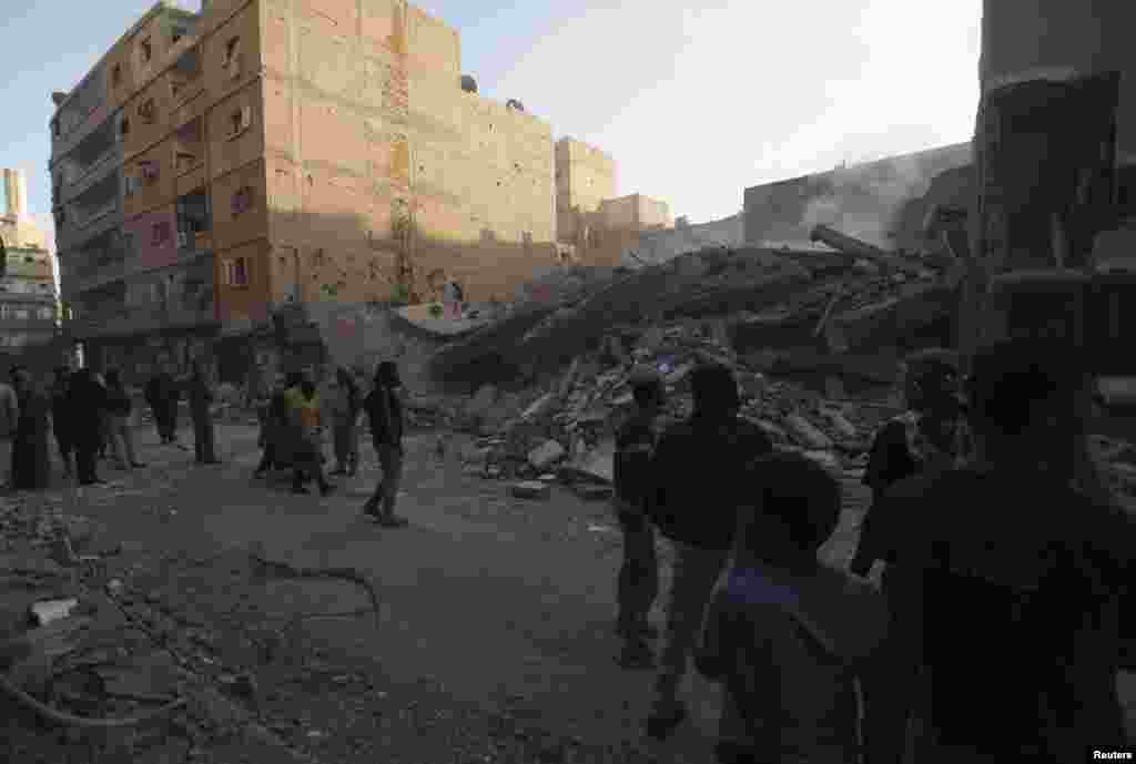 Civilians gather at a site of a collapsed building that activists said was shelled by forces loyal to Syria's President Bashar al-Assad in Deir al-Zor, October 14, 2013.