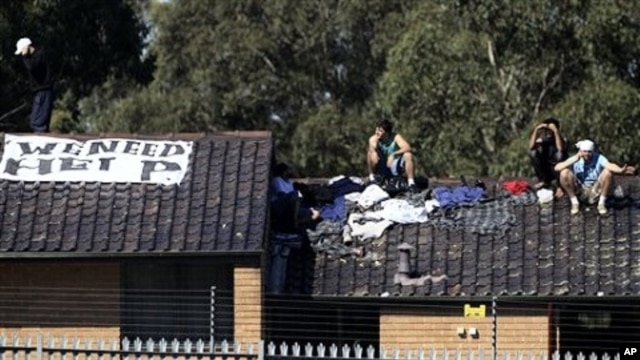 Five detainees gather on a rooftop of the Villawood Detention Center in Sydney, Australia, April 21, 2011