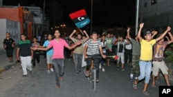 People in Tajura, a suburb of Tripoli, celebrating in the early morning on August 22, 2011 after Libyan rebels surged into Tripoli in a final drive to oust leader Gadhafi