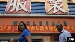 Deux Africains marchent devant un magasin à Guangzhou, Chine, le 26 août 2013.