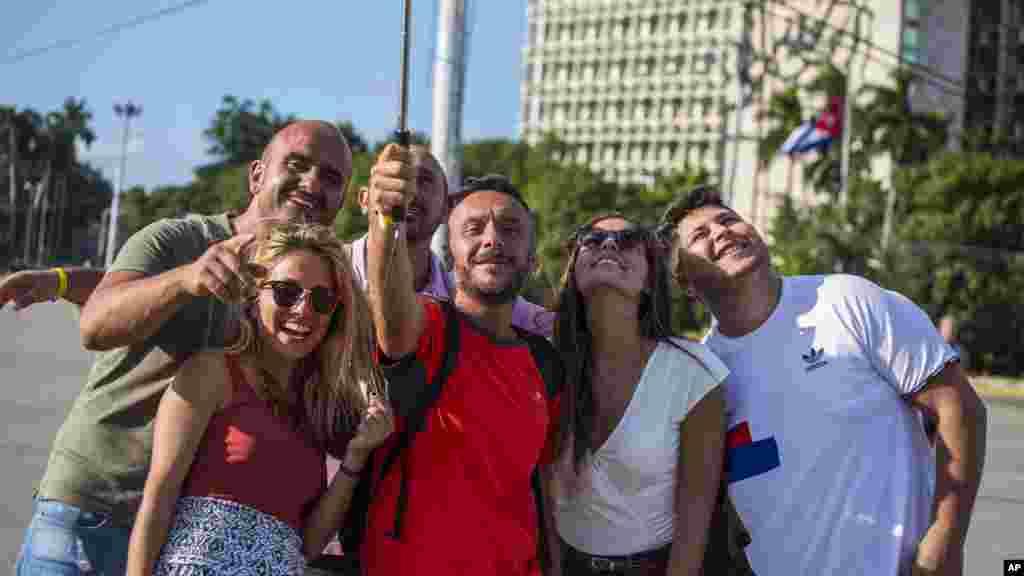 """Les touristes prennent des selfies avec une image du héros révolutionnaire cubain Ernesto """"Che"""" Guevara à la place de la révolution à La Havane, Cuba, le 27 novembre 2016."""