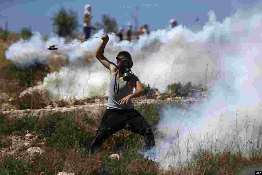 A Palestinian protester hurls back a tear gas canister fired by Israeli troops during a demonstration by in the village of Nabi Saleh, north of Ramallah, in the Israeli-occupied West Bank.