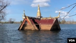 A curving roof of a small wooden pagoda juts above the water line in Srekor village of Stung Treng province, which has been affected flooding caused by Lower Sesan 2 Dam, Nov 28, 2018. (Sun Narin/VOA Khmer)