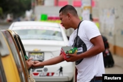 A Venezuelan migrant sells candy at a street in Tumbes, Peru, Aug. 25, 2018.