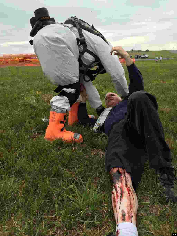 "A Pennsylvnaia National Guard member in a protective HAZMAT suit assists a ""victim,"" Ft. Indiantown Gap, Pennsylania, Aug. 20, 2014. (Carolyn Presutti/VOA)"