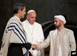 Pope Francis looks at Imam Khalid Latif, right, and Rabbi Elliot J. Cosgrove, left, shaking hands as he arrives for an interfaith service at the Sept. 11 memorial museum in New York, Sept. 25, 2015.