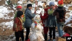 Syrian refugees children play near a snowman in a camp for Syrians who fled their country's civil war, in the Bekaa valley, eastern Lebanon, Dec. 12, 2013.