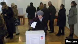 A woman casts her ballot at a polling station during the presidential election in Zagreb December 28, 2014. Croats were voting for a new head of state on Sunday but none of the four candidates for the largely ceremonial post in the European Union's newest