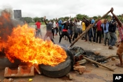 FILE - Protesters gather near a burning tire during a demonstration over the hike in fuel prices in Harare, Zimbabwe, Jan. 15, 2019.