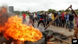 FILE: Protestors gather near a burning tire during a demonstration over the hike in fuel prices in Harare, Zimbabwe, Tuesday, Jan. 15, 2019. A Zimbabwean military helicopter on Tuesday fired tear gas at demonstrators blocking a road and burning tires in the capital.