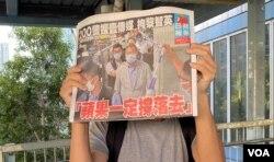 市民在天水围西铁站外领取8月11日的免费苹果日报,高举头版以示支持。 (美国之音汤惠芸)