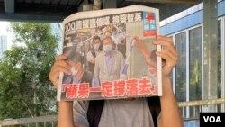 市民在天水圍西鐵站外領取8月11日的免費蘋果日報,高舉頭版以示支持。(美國之音湯惠芸)