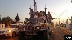 ພວກນັກຕໍ່ສູ້ ຈາກກຸ່ມລັດອິສລາມ ພາກັນສະເຫລີມສະຫລອງ ຫຼັງຈາກທີ່ສາມາດຢຶດເອົາລົດ ຈາກກຳລັງຮັກສາຄວາມໝັ້ນຄົງຂອງອີຣັກ ມາໄດ້ ຢູ່ໃນເມືອງ Mosul ປະເທດອີຣັກ.