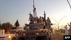FILE - Fighters from the Islamic State group parade in a commandeered Iraqi security forces vehicle in Mosul, Iraq.
