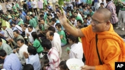 A Cambodian Buddhist monk sprinkles holly water to villagers who set a prayer rally to save rain forests in front of Royal Palace in Phnom Penh, Cambodia, Thursday, Aug. 18, 2011. Hundreds of villagers prayed at the spirit's shrine, demanding the governme