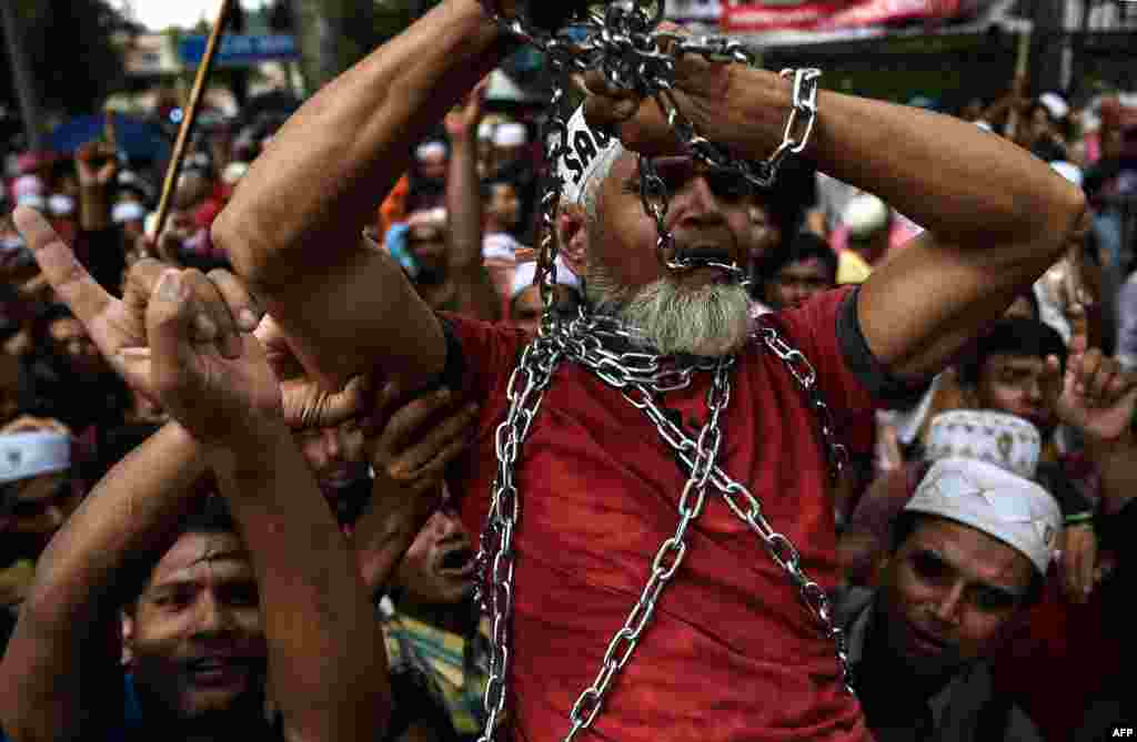 Ethnic Rohingya Muslim refugees shout slogans as they carry a man in chains during a protest against the persecution of Rohingya Muslims in Myanmar, outside the Myanmar Embassy in Kuala Lumpur.