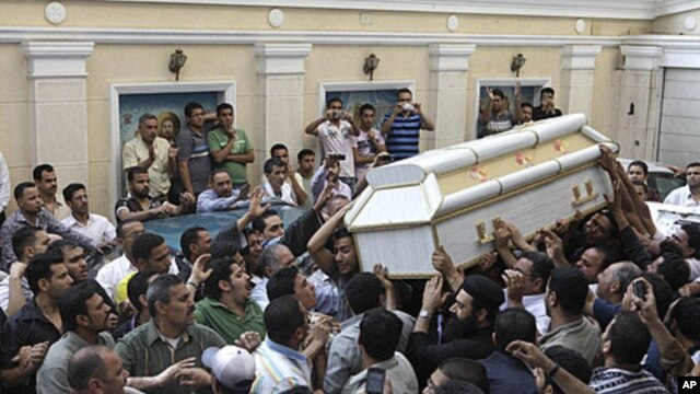 Egyptian Christians carry the coffin of one of the victims of Saturday night's clashes with Muslims in the streets of western Cairo, during a funeral ceremony at Giza church, Sunday, May 8, 2011