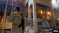 solda libyen kanpe devan yon bilding aprè yon atak ayeryen (AP Photo/Darko Bandic)