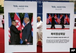 Photos of the summit between U.S. President Donald Trump and North Korean leader Kim Jong Un are displayed during a photo exhibition to wish for peace on the Korean Peninsula in Seoul, South Korea, Sept. 19, 2018.