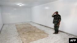 Pripadnik libijskih revolucionarnih snaga u praznom skladištu-hladnjači gde je bilo izloženo telo bivšeg libijskog lidera Moamera Gadafija, 25. oktobar 2011.