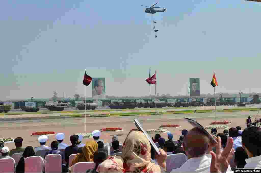 پریڈ میں شامل ایک ہیلی کاپٹر فوجیوں کو رسے سے لٹکائے جا رہا ہے