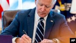 ប្រធានាធិបតីសហរដ្ឋអាមេរិកលោក Joe Biden ចុះហត្ថលេខាលើសេចក្តីព្រាងច្បាប់ American Rescue Plan ដែលជាកញ្ចប់ជំនួយសម្រាប់វិបត្តិជំងឺកូវីដ១៩ ឲ្យក្លាយទៅជាច្បាប់ នៅការិយាល័យរបស់លោកក្នុងសេតវិមាន នៅរដ្ឋធានីវ៉ាស៊ីនតោន ថ្ងៃទី១១ ខែមីនា ឆ្នាំ២០២១។