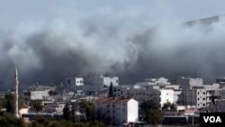 Khói bốc lên bao phủ bầu trời sau các vụ không kích ở thị trấn Kobani.