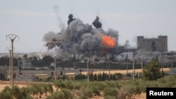 FILE - Smoke and flame rise after what fighters of the Syria Democratic Forces said were U.S.-led airstrikes on the mills of Manbij where Islamic State militants are positioned, in Aleppo Governorate, Syria, June 16, 2016.