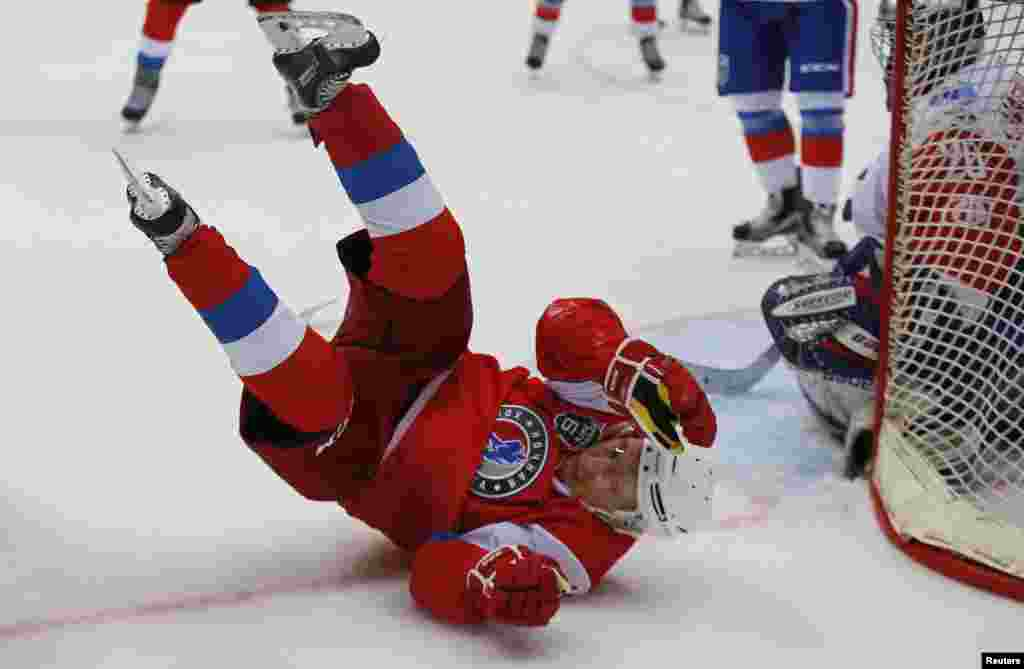 Russian President Vladimir Putin falls as he takes part in a gala match of the hockey teams of the Night League at the Shayba Olympic Arena in Sochi, Russia, May 10, 2017..