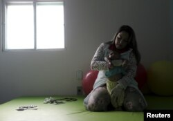Physiotherapist Jeime Lara Leal does exercises with Lucas, 4-months old, who is Miriam Araujo's second child and born with microcephaly in Pedro I hospital in Campina Grande, Brazil, Feb. 17, 2016.
