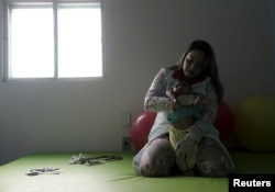 Physiotherapist Jeime Lara Leal does exercises with Lucas, 4 months old, who is Miriam Araujo's second child and born with microcephaly in Pedro I hospital in Campina Grande, Brazil, Feb. 17, 2016.