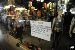 "FILE - A sign in the window of a closed clothing store in a Latino mall in Atlanta, July 1, 2011, shows support for ""A Day Without Immigrants,"" in which a Georgia Latino group is calling on businesses to close and community members to not work or shop."